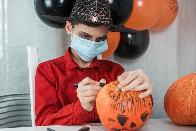 Adolescent en costume et masques pour se protéger du covid-19 dessinant une citrouille pour la célébration d'halloween
