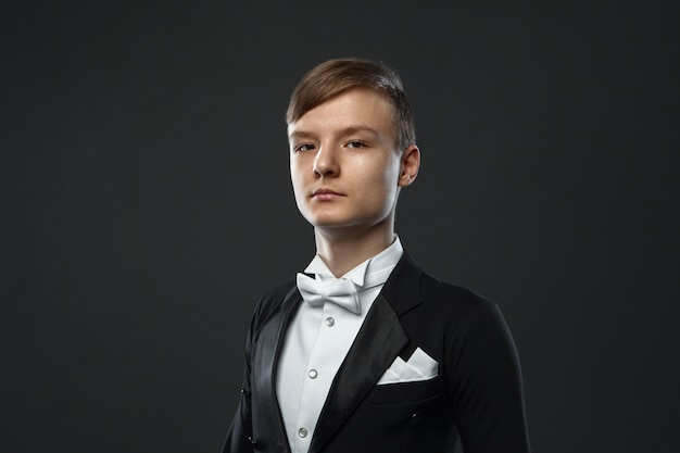 Adolescent en costume sur un mur noir