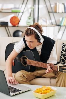 Adolescent dans des écouteurs sans fil de manger des chips lors de l'apprentissage de la lecture d'une nouvelle chanson à la guitare acoustique