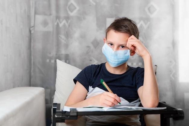 Un adolescent dans un masque jetable fait ses devoirs sur le canapé.