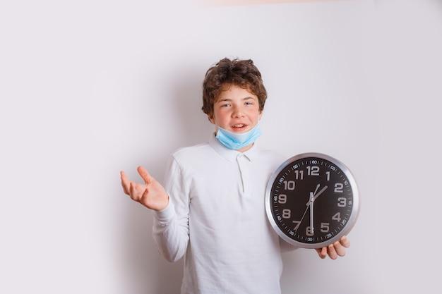 Un adolescent dans un masque médical tient une montre