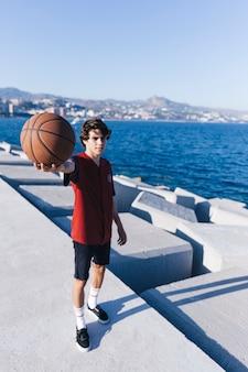 Adolescent, debout, mer, projection, basket-ball