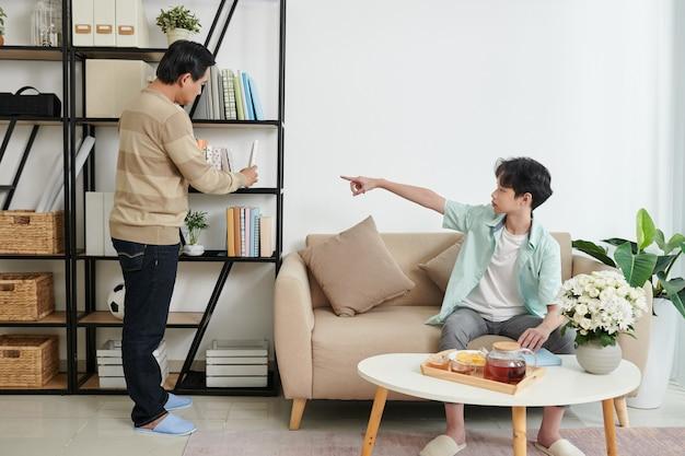 Un adolescent demande à son père de lui donner un livre sur une étagère lorsqu'ils lisent et boivent du thé à la maison