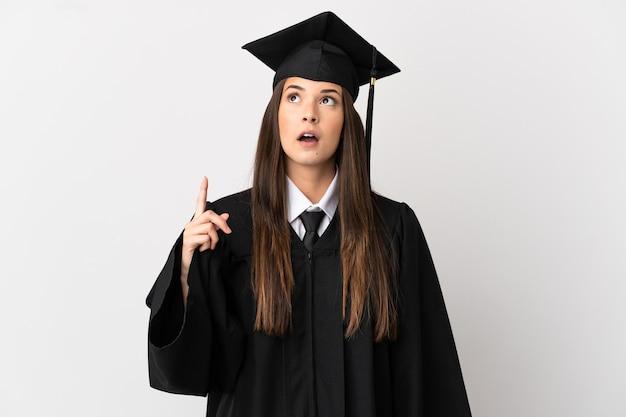 Adolescent diplômé de l'université brésilienne sur fond blanc isolé pensant une idée pointant le doigt vers le haut