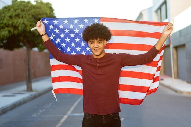 Adolescent avec un drapeau américain ouvert