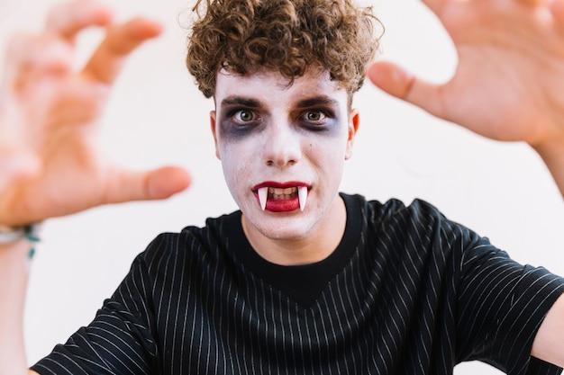 Adolescent avec du maquillage d'halloween et des crocs de vampire