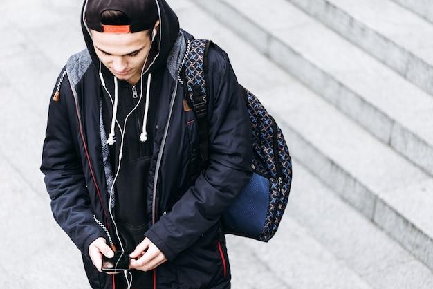 Adolescent écoutant de la musique et utilisant un téléphone dans un environnement urbain