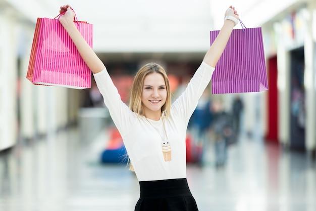 Adolescent enjoueur dansant avec des sacs à provisions