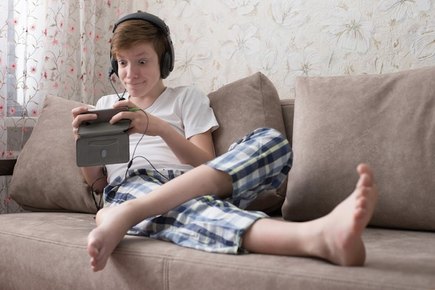 Adolescent est assis sur le canapé et regarde la vidéo sur le téléphone avec un visage surpris