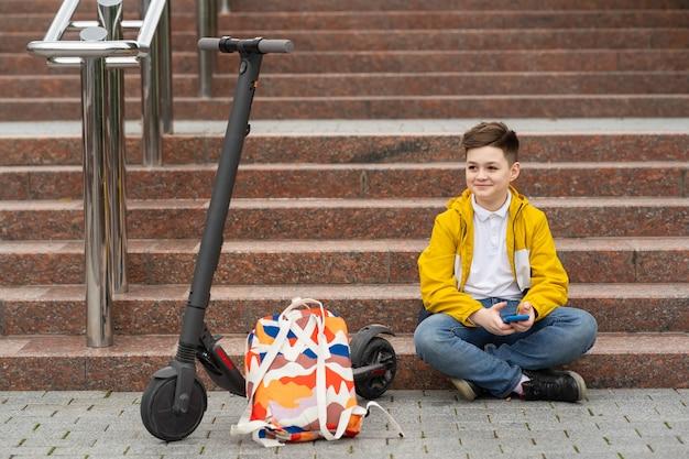 Adolescent est assis dans les escaliers avec téléphone mobile