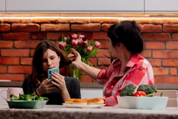 L'adolescent est assis avec le téléphone à côté de sa grand-mère et ne fait pas attention à elle