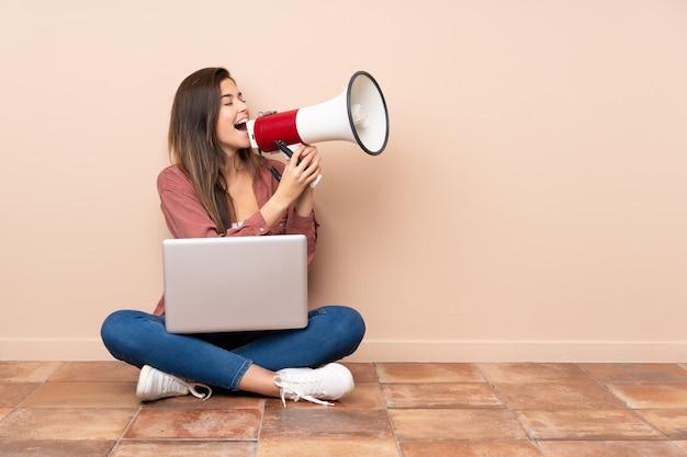 Adolescent étudiant femme assise sur le sol avec un ordinateur portable criant à travers un mégaphone