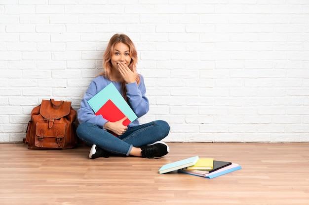 Adolescent étudiant fille aux cheveux roses assis sur le sol à l'intérieur heureux et souriant couvrant la bouche avec la main