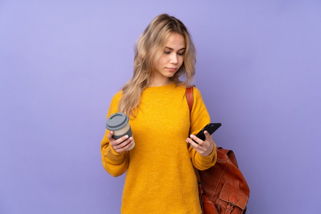 Adolescent étudiant fille sur violet tenant du café à emporter et un mobile