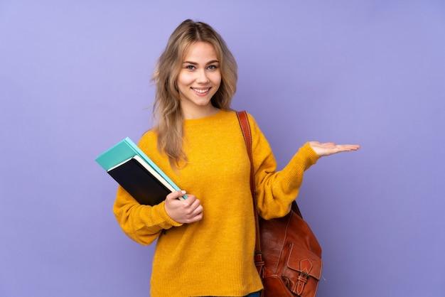 Adolescent étudiant fille sur violet tenant imaginaire sur la paume pour insérer une annonce