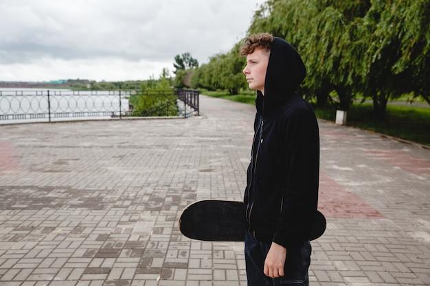 Un adolescent européen aux cheveux bouclés dans un sweat à capuche noir avec un patin dans les mains se tient sur le remblai...