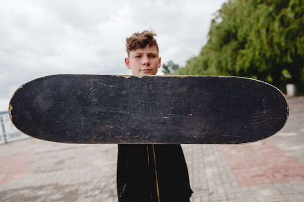 Un adolescent européen aux cheveux bouclés tient un vieux patin noir et minable devant lui, seul le patin est au point ...