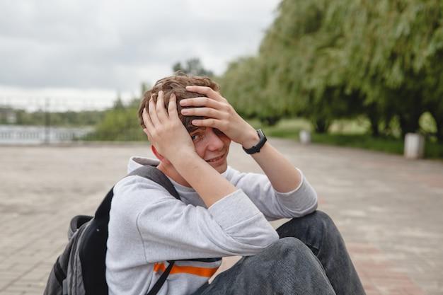 Un adolescent européen riant aux cheveux bouclés dans un jean gris et avec une sacoche sur le dos est si ...