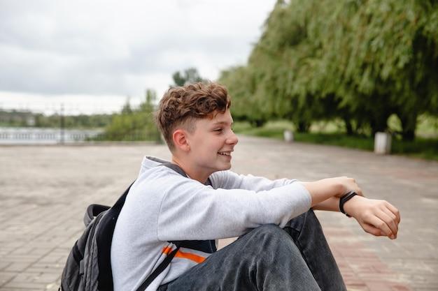 Un adolescent européen riant aux cheveux bouclés vêtu d'un jean gris et d'une sacoche sur le dos est assis...