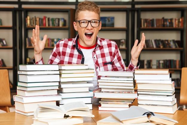 Adolescent excité assis à la bibliothèque