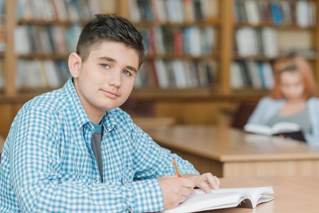 Adolescent, faire ses devoirs dans la bibliothèque
