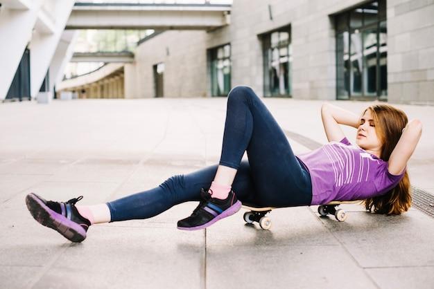 Adolescent faisant des craquements abdominaux sur la planche à roulettes