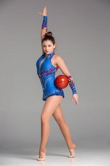 Adolescent faisant la danse de gymnastique avec la boule de gymnastique rouge sur un fond gris