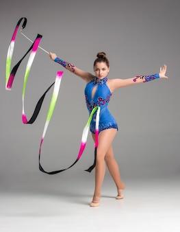 Adolescent faisant la danse de gymnastique avec le ruban coloré sur un fond gris