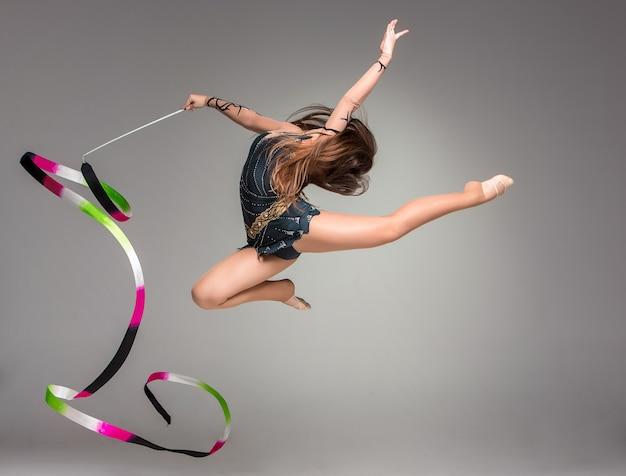 Adolescent faisant la danse de gymnastique avec le ruban
