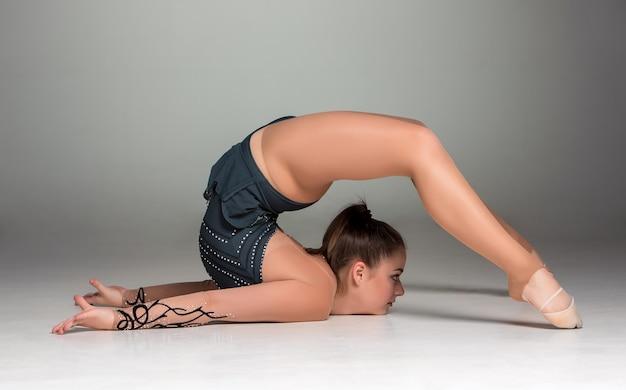 Adolescent faisant des exercices de gymnastique sur fond gris