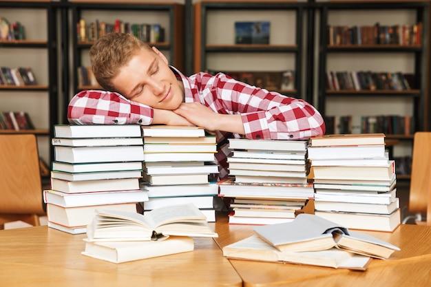 Adolescent fatigué assis à la bibliothèque