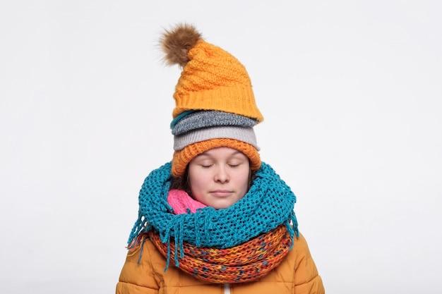 Adolescent femelle caucasien drôle dans plusieurs écharpes et chapeaux se détendre avec les yeux fermés.