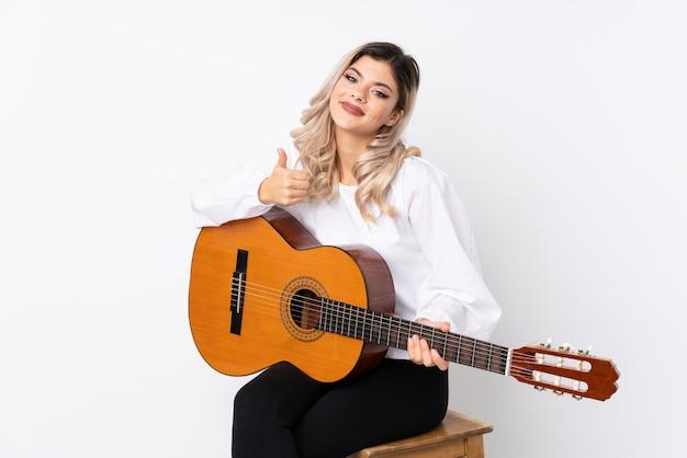 Adolescent femme avec guitare sur blanc isolé avec les pouces vers le haut parce que quelque chose de bien s'est produit