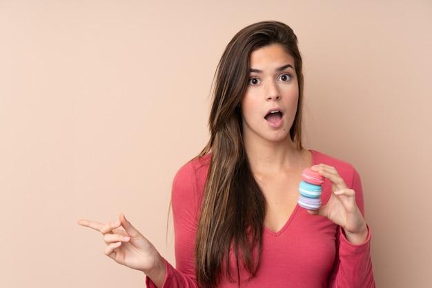 Adolescent, femme, isolé, mur, tenue, coloré, français, macarons, pointage, côté