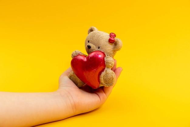 Adolescent femme main tenir un petit ours en peluche jouet avec coeur rouge sur fond jaune, vue de dessus. concept de la saint-valentin.