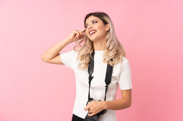 Adolescent femme sur rose isolé avec un appareil photo professionnel et la pensée