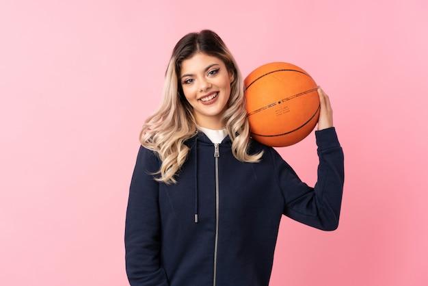 Adolescent femme sur rose isolé avec ballon de basket