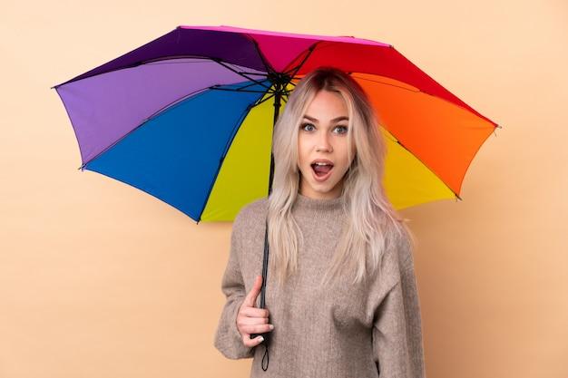 Adolescent femme tenant un parapluie sur un mur isolé avec une expression faciale surprise