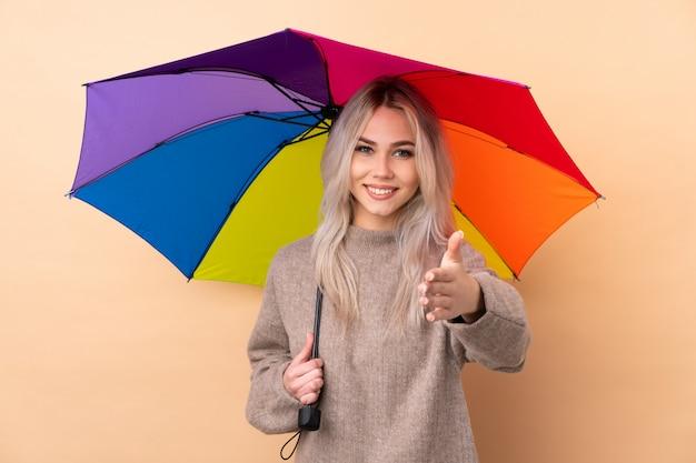 Adolescent femme tenant un parapluie sur le mur isolé poignée de main après une bonne affaire