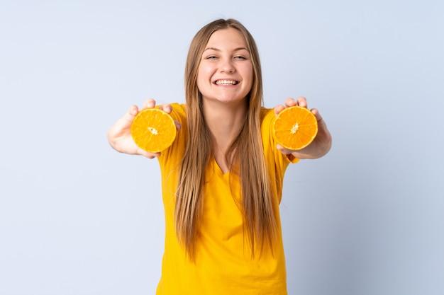 Adolescent femme ukrainienne isolée sur un espace bleu tenant une orange