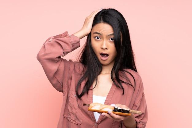 Adolescent fille asiatique manger des sushis sur mur rose avec une expression faciale surprise