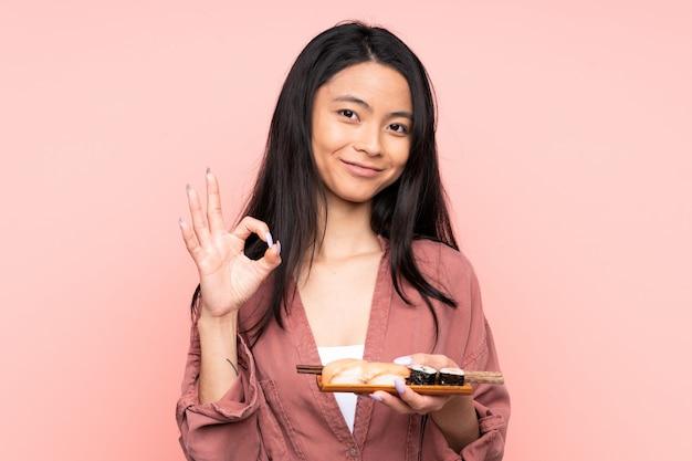 Adolescent fille asiatique manger des sushis sur mur rose montrant un signe ok avec les doigts