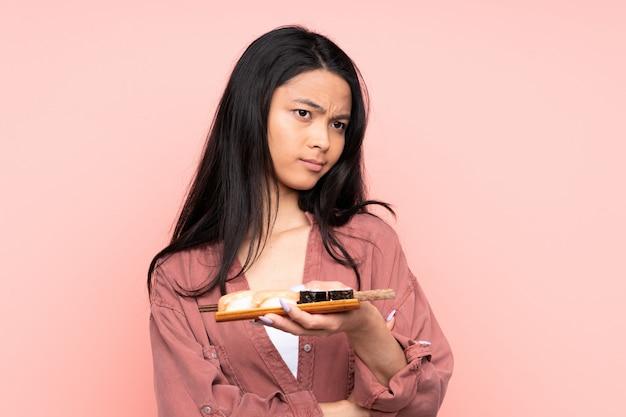 Adolescent fille asiatique manger des sushis sur mur rose en pensant à une idée