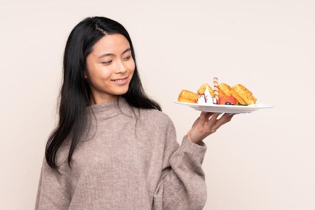 Adolescent fille asiatique tenant des gaufres sur mur beige avec une expression heureuse