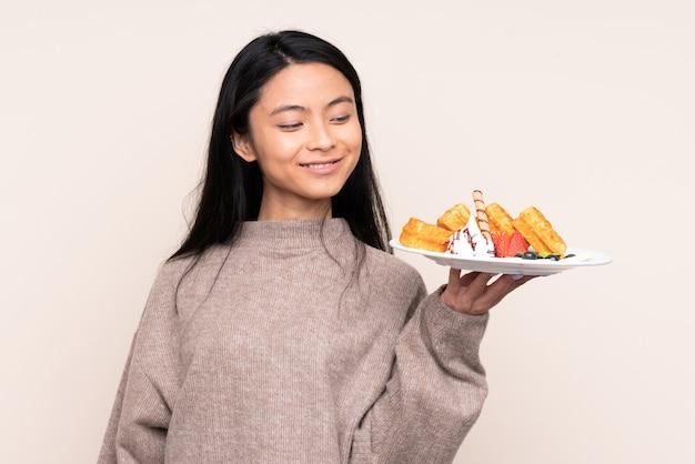 Adolescent fille asiatique tenant des gaufres sur un mur beige avec une expression heureuse