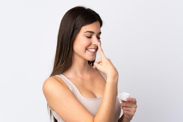 Adolescent fille brésilienne avec crème hydratante sur mur blanc isolé