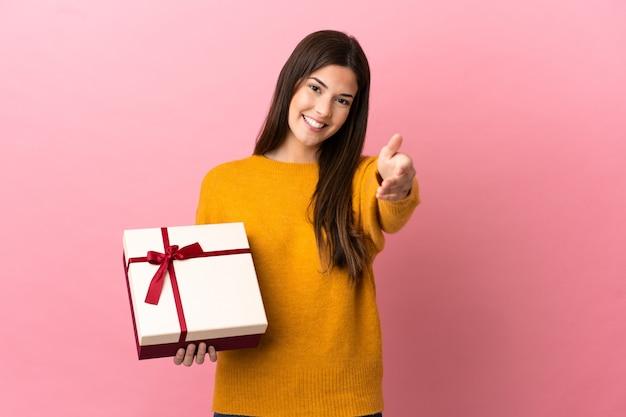 Adolescent fille brésilienne tenant un cadeau sur fond rose isolé se serrant la main pour conclure une bonne affaire