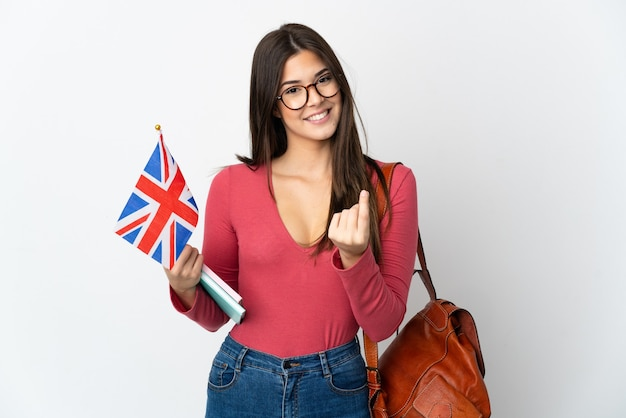 Adolescent fille brésilienne tenant un drapeau du royaume-uni isolé sur blanc faisant le geste de l'argent