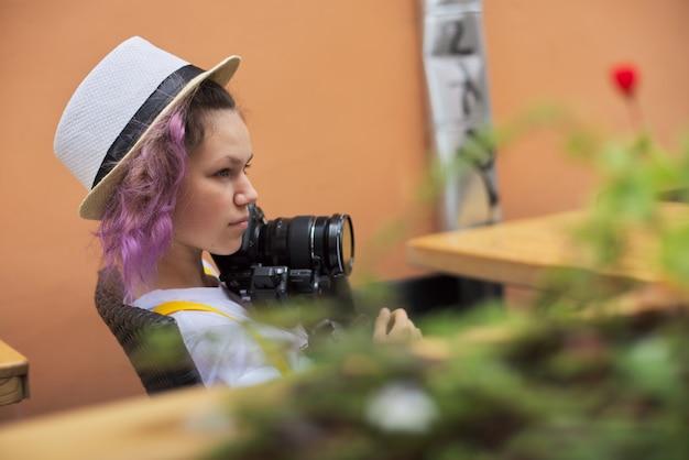 Adolescent fille avec caméra assis dans un café en plein air de la ville