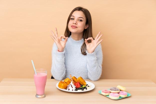Adolescent fille mangeant des gaufres sur beige montrant un signe ok avec les doigts